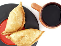 Empanada - Argentine fried meat pies on plate with black coffee isolated on white background Stock Photos