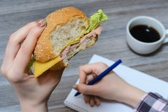 Snack food fast eating essay inspiration idea concept. Cropped close up overhead photo of close up photo of bitten burger in stude. Nt`s hand. Student writing Royalty Free Stock Photo