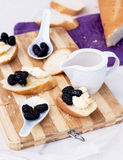 Snack on french baguette on a wooden board. Mulberry Stock Image