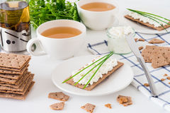Snack with fresh tea and rye crispy bread Swedish crackers with cottage cheese, decorated with thin green onion, on white backgr. Snack with fresh tea and rye royalty free stock images