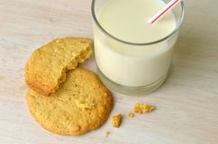 A snack of homemade peanut butter cookies ready to eat and a fresh glass of milk ready to drink through a straw. Stock Images