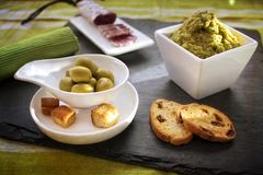 Snack in a late afternoon. Scene of a late afternoon Mediterranean snack with green olives, croutons, chorizo and tapenade royalty free stock photo