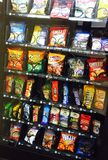 Snack Food Vending Machine. Convenient Snack machine full of snicker bar, Cheez-it, Oreos Fritos, Chex mix, slim Jim, bugles, Twix, Starburst, beef jerky, and Royalty Free Stock Image