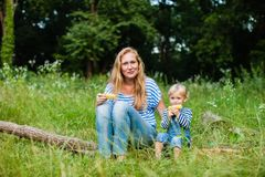 Snack on the nature. Mom with dauther sitting on a fallen tree trunk and eating corn Stock Photo