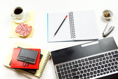 A snack next to the laptop, notebooks, stationery. Royalty Free Stock Image