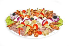 Snack plate. Mixed snack plate with salami, onions, pickles, red pepper, feta cheese, olives and green salad leaves Royalty Free Stock Photo