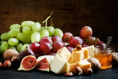 Snack plate for wine: cheese, green and pink grapes, figs, nuts stock photos
