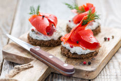 Snack rye bread, soft cheese with herbs and salted red salmon. Snack rye bread, soft cheese with herbs and salted red salmon on a cutting board Royalty Free Stock Photo