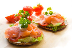 Snack with salmon. A fresh summer snack with smoked salmon on rye bread with lettuce leaves, white sauce, tomatoes and parsley. The snacks are located in a royalty free stock photo