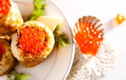 Snack with salmon caviar and pancakes. Rolled snack with salmon caviar and russian pancakes Royalty Free Stock Images