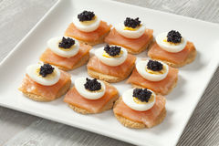 Snack with salmon,quail eggs and lumpfish roe. On toast Royalty Free Stock Images