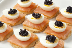 Snack with salmon,quail eggs and lumpfish roe. On toast Stock Images