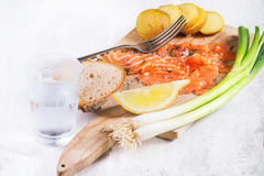 Snack with salted salmon. Sliced salted salmon with potatoes, bread, green onion and frozen glass of vodka served on old wooden cutting board over white wooden Royalty Free Stock Photo