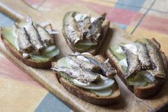 Snack sandwiches with sprats and pickles Stock Image