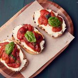 Snack set. Brushetta with cherry tomatoes, garlic, cream cheese and basil. Slow food, party food concept royalty free stock photos