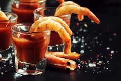 Snack with shrimp and spicy tomato cocktail, black kitchen table, selective focus. Snack with shrimp and spicy tomato cocktail, black kitchen table,  selective royalty free stock image