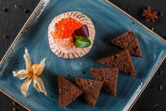 Snack from shrimps and red caviar with black bread, decorated with physalis and greens on plate over black background. Healthy food stock photo