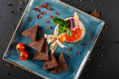 Snack from shrimps and red caviar with black bread, decorated with physalis and greens on plate over black background.Healthy food. Snack from shrimps and red royalty free stock photos