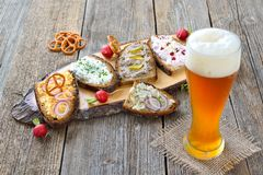 Snack with spreads. Hearty snack with different kinds of spreads on farmhouse bread served with a fresh Bavarian yeast wheat beer on an old wooden table Stock Images