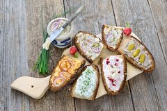 Snack with spreads. Hearty snack with different kinds of spreads on farmhouse bread served on an old wooden table Stock Image