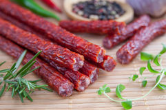Snack stick sausage. On a bamboo mat Royalty Free Stock Photography