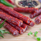 Snack stick sausage. On a bamboo mat Royalty Free Stock Image