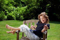 Snack time. Young girl giggling in the garden with an afternoon snack stock photography