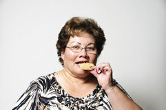 Snack time. An older Hispanic woman eating a cookie for a snack Stock Photos