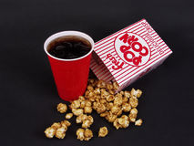 Snack Time. A spilled box of caramel corn and a red cup of soda on a black background Royalty Free Stock Images