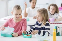 Snack time in a kindergarten class. Children opening their mint royalty free stock photo