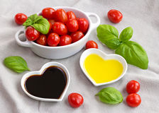 Snack tomatoes, basil, oil and vinegar to make a healthy salad Stock Photo