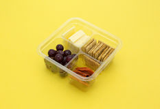 Snack tray in plastic container on yellow table top Royalty Free Stock Images