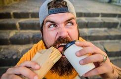 Snack voor goede stemming Het concept van het straatvoedsel Gebaarde de mens eet smakelijke worst en drankdocument kop Stedelijke royalty-vrije stock afbeelding