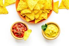 Snack voor partij Mexicaanse nachos dichtbij salsa en guacamole sause op witte hoogste mening als achtergrond stock afbeeldingen