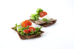 Snack from wholegrain rye crispbreads with Cherry tomatoes, salad and goat cheese. Healthy snack from wholegrain rye crispbreads crackers with Cherry tomatoes stock images