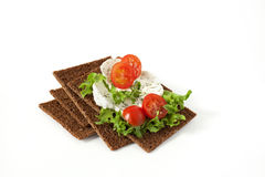 Snack from wholegrain rye crispbreads with Cherry tomatoes, salad and goat cheese. Healthy snack from wholegrain rye crispbreads crackers with Cherry tomatoes Stock Photo
