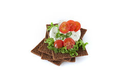 Snack from wholegrain rye crispbreads with Cherry tomatoes, salad and goat cheese royalty free stock image