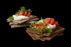 Snack from wholegrain rye crispbreads with Cherry tomatoes, salad and soft cheese. Healthy snack from wholegrain rye crispbread cracker with Cherry tomatoes stock photos