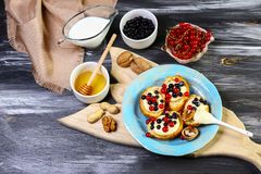Snack for wine. Bruschetta with blueberries, and red currant, cream cheese ricotta. Top flat view on wooden background stock image