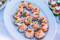 Snackh con los salmones en las placas blancas Imagenes de archivo