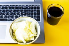 Snacking with junk food at the laptop. Chips and cola are near the laptop. Junk food. Snack in the break between work Royalty Free Stock Photography