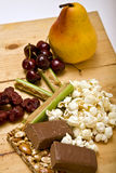 Snacks. Healthy alternative snacks and foods such as fruit (pear and cherries), popcorn, celery and peanut butter, nutbar, food bar and jerky Royalty Free Stock Image
