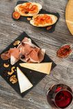 Snacks and appetizer, cheese, jamon, nuts, bruschettas and red w Stock Photography