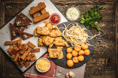 Snacks for beer. Different food cooked on the grill on a wooden table, grilled crackers toast cheese sauce greens Outdoors Food Concept Royalty Free Stock Image
