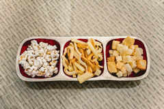 Snacks for beer. Different sorts of snacks for beer on the table of summer caffee. Cheese, popcorn and bread crackers Royalty Free Stock Photography
