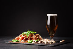 Snacks for beer. A glass full of beer and foam, pistachios and prosciutto seasoned with pepper and basil on a dark Stock Images