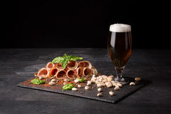 Snacks for beer. A glass full of beer and foam, pistachios and prosciutto seasoned with pepper and basil on a dark Stock Photo