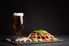 Snacks for beer. A glass full of beer and foam, pistachios and prosciutto seasoned with pepper and basil on a dark Royalty Free Stock Photography