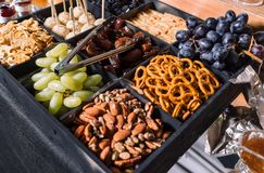 Snacks for beer-grapes, almonds, dates. royalty free stock photography
