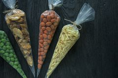 Snacks for beer. Set for beer. Nuts, crackers, fried potatoes in strips. View from above. Space for text. Dark wooden background royalty free stock images
